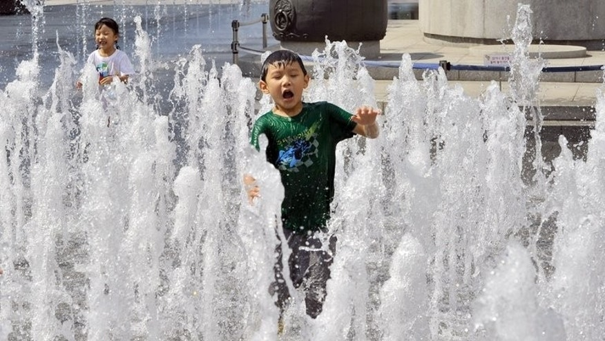 Children play in a public water fountain in Seoul on a hot summer's day, on June 10, 2013. South Korea is in the grip of an extended heatwave and a lengthy disruption in its nuclear power sector.