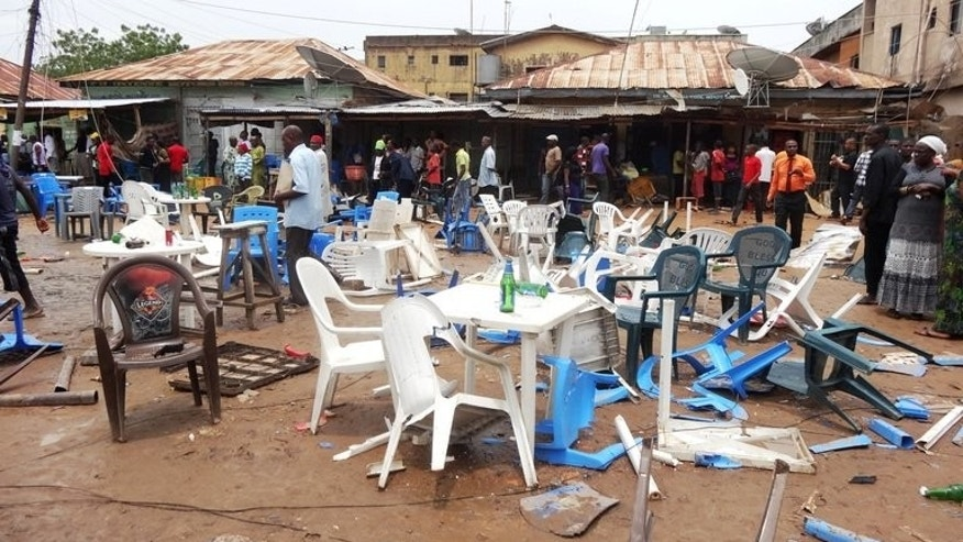 People gather at the scene of an explosion targeting an open-air beer garden at Enugu Road in the downtown Sabon Gari neighbourhood of Kano on July 30, 2013. The leader of Nigeria's Boko Haram Islamists has claimed a series of recent deadly attacks on security forces in the northeast, in a video obtained by AFP Monday.