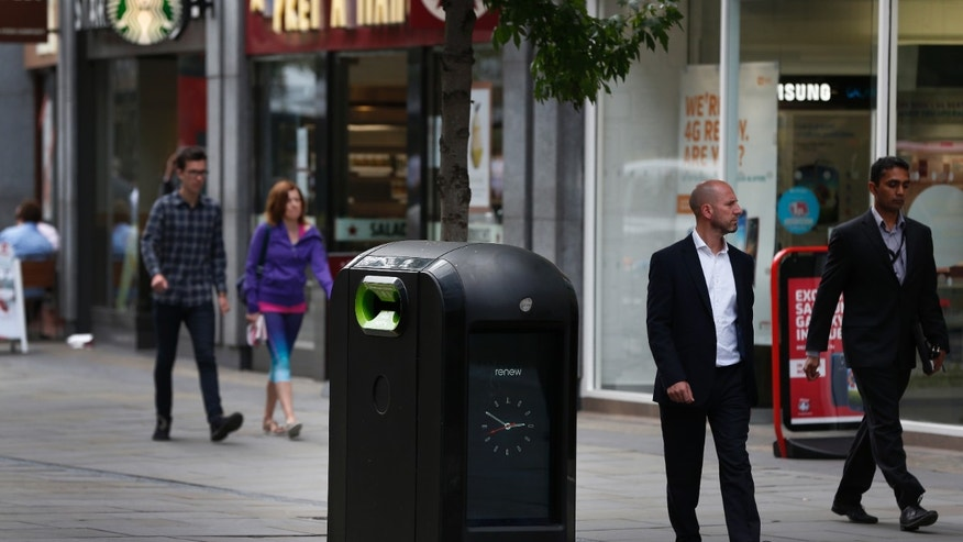 Aug. 12, 2012 - People walk past a trash bin in central London. Officials say an advertising firm must immediately stop using its network of high-tech trash cans, like this one, to track people walking through London's financial district.