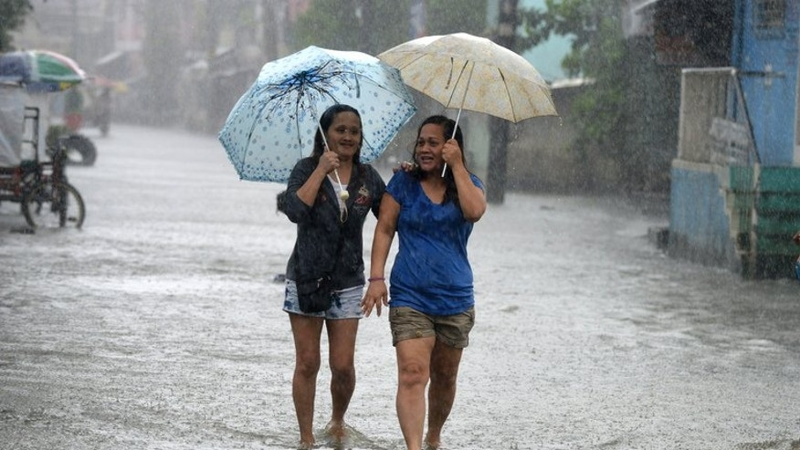 Residents wade through ankle-deep water along a flooded stretch of road as heavy rains brought on by Typhoon Utor hit the suburbs of Manila on August 12, 2013. The strongest typhoon to hit the Philippines this year flattened houses, caused flash floods and triggered landslides in remote towns on Monday, killing at least one person.