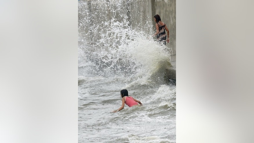 Young people play in the waves brought on by Typhoon Utor as the ocean splashes up along a sea wall in the suburbs of Manila on August 12, 2013. villages that were in Utor's direct path until Tuesday. Hundreds of people die each year in the Philippines from the roughly 20 typhoons that strike the country.