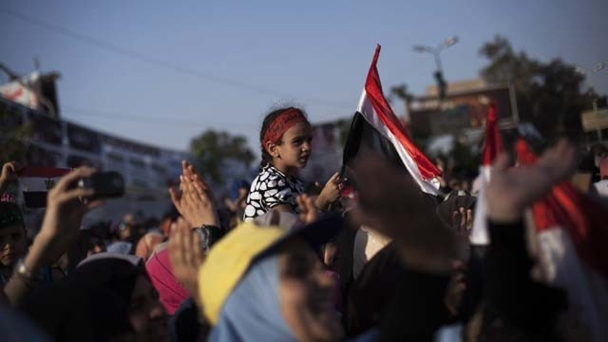 August 11, 2013: An Egyptian girl waves a national flag while supporters of Egypt's ousted President Mohammed Morsi chant slogans against the Egyptian Army at the sit-in at Rabaah al-Adawiya mosque, which is fortified with multiple walls of bricks, tires, metal barricades and sandbags, and where protesters have installed their camp in Nasr City, Cairo. (AP Photo)