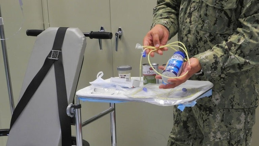 A US naval medic holds liquid food supplement force fed to hunger strikers at the US Naval Base in Guantanamo Bay, Cuba on August 7, 2013. One Yemeni prisoner at Guantanamo Bay says it is an agonizing, cruel punishment that he would not wish on anyone. But for staff at the controversial US military jail, the criticisms of feeding by tubes are overblown.