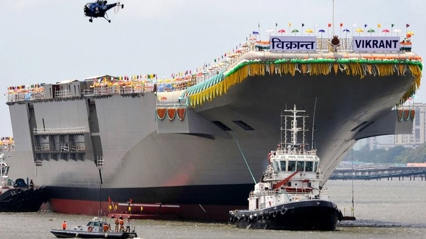 Tugboats guide the aircraft carrier INS Vikrant as it leaves the Cochin Shipyard in Kochi on August 12, 2013. When the INS Vikrant comes into full service in 2018, India will become the fifth nation to have designed and built its own aircraft carrier, pushing ahead of China to join an elite club that includes Britain, France, Russia and the United States.