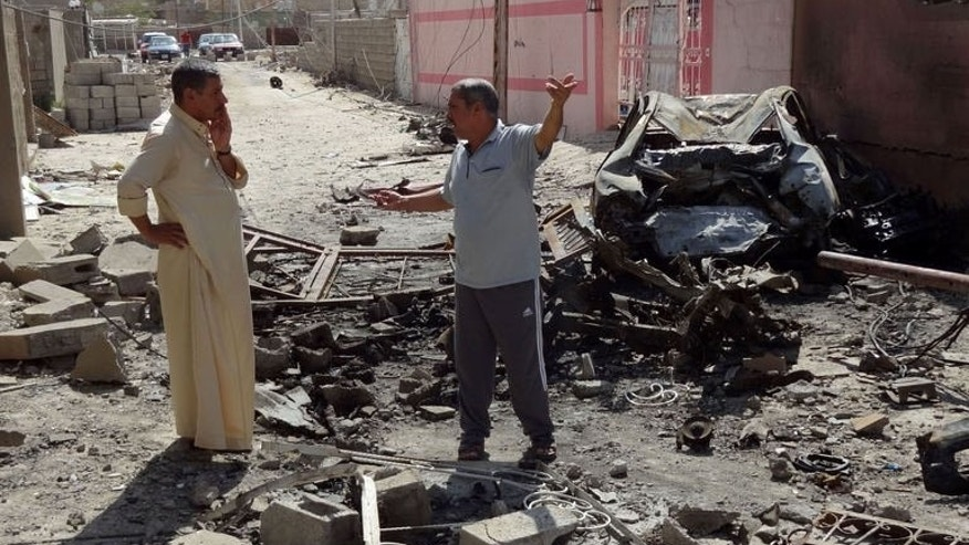 Iraqis talk on the site where a suicide bomber detonated the day before an explosives-rigged vehicle on August 11, 2013 in the northern city of Tuz Khurmatu. Bombers killed 24 people in Iraq on Monday, 16 of them in a suicide attack on a cafe north of Baghdad, officials said.