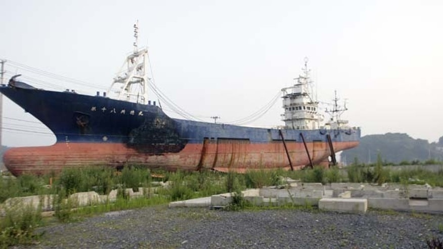 August 11, 2013: A stranded fishing boat stands in Kesennuma, Miyagi prefecture, northern Japan. (AP Photo)