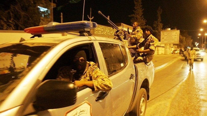 Members of the Libyan security forces drive through Benghazi, in May 2013. A journalist at a private Libyan television channel narrowly survived an assassination attempt in the restive Benghazi, a colleague working for the Libya al-Ahrar TV network told AFP.