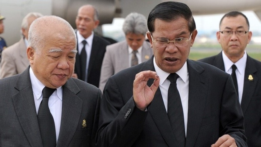 Cambodian Prime Minister Hun Sen (R) speaks to Prince Norodom Chakrapong at Phnom Penh International Airport on August 12, 2013. Cambodia's strongman Prime Pinister Hun Sen narrowly won the popular vote in recent disputed elections, according to preliminary.