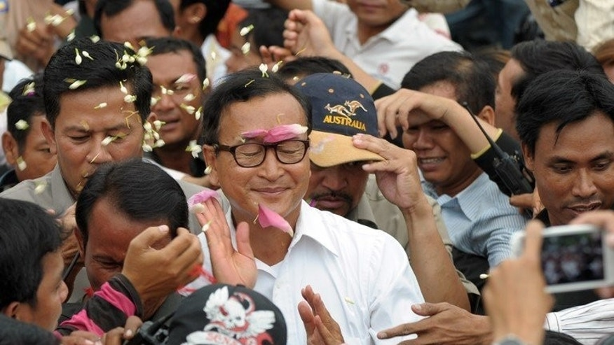 Sam Rainsy (C), leader of the opposition Cambodia National Rescue Party (CNRP), greets people during a rally at Democracy Park in Phnom Penh on August 6, 2013. Rainsy party immediately disputed preliminary results that gave Hun Sen victory.
