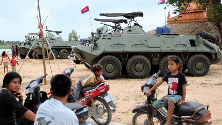 Children on motobikes near armoured vehicles in Phnom Penh on August 8, 2013, after they were deployed in case of unrest. The opposition says it wants to resolve election issues peacefully and will only demonstrate as a last resort.