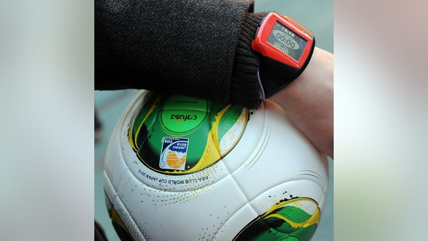 "A FIFA officer displays a watch displaying ""goal"" and a ball during a demonstration of new goal-line technology by Hawk-Eye Innovations in Aichi December 8, 2012. When a goal is scored, a signal will be sent to the match officials' wristwatches within a second."