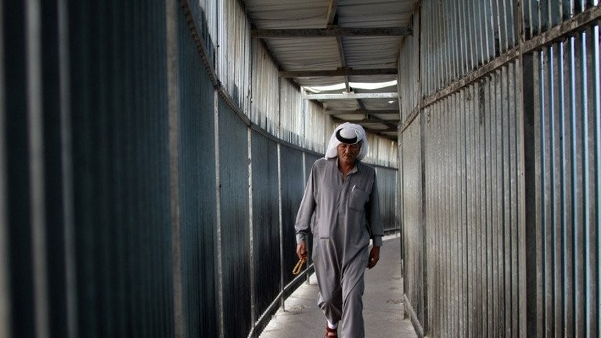 A Palestinian Muslim crosses a checkpoint along Israel's controversial separation barrier on the outskirts of the West Bank town of Bethlehem on July 12, 2013. Israel announced it will release 26 veteran Palestinian prisoners ahead of a resumption of peace talks on Wednesday, but at the same time angered Palestinians by approving new settlement construction.