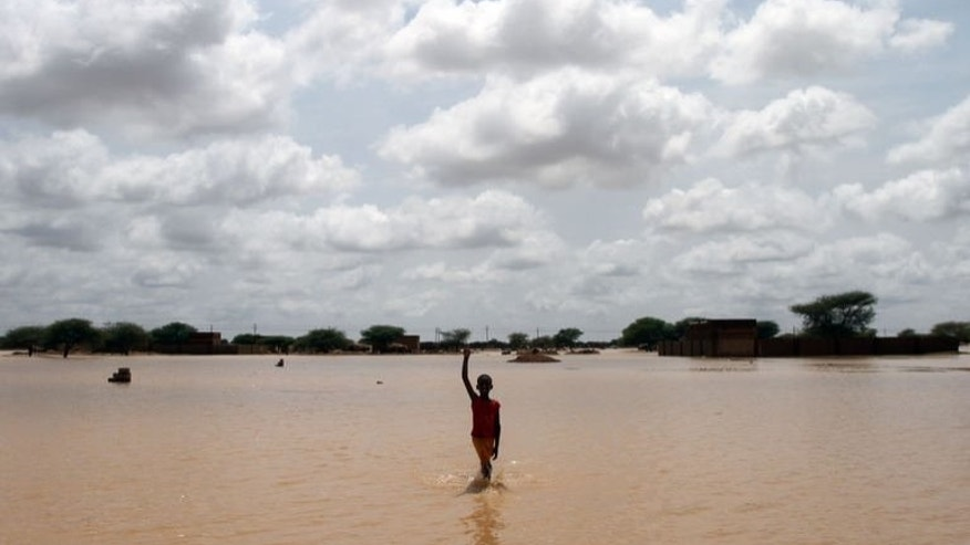 A young Sudanese boy points to the sky as he walks through a flooded street on the outskirts of the capital Khartoum on August 10, 2013. Drainage is poor in the capital, where even a little rain can cause flooding but this year's water surge was unusually severe.