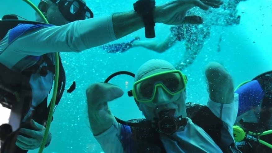 Philippe Croizon celebrates underwater on January 10, 2013 after becoming the first quadruple amputee to dive to a depth of 33 metres, in the deepest swiming pool in the world in Brussels.