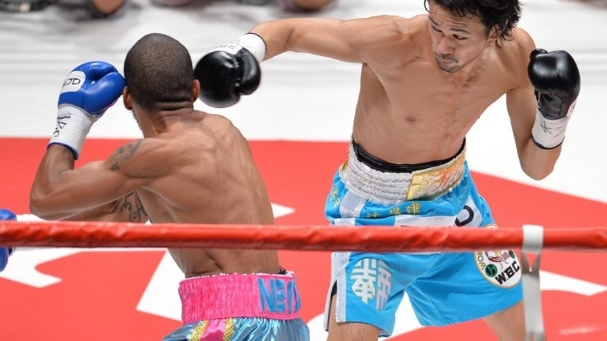 WBC bantamweight champion Shinsuke Yamanaka of Japan (R) connects with a right to Jose Nieves of Puerto Rico (L) in the first round of their WBC bantamweight title boxing bout in Tokyo on August 12, 2013. Yamanaka knocked out Nieves with a lightning straight left in the first round to retain his World Boxing Council bantamweight title in Tokyo on Monday.