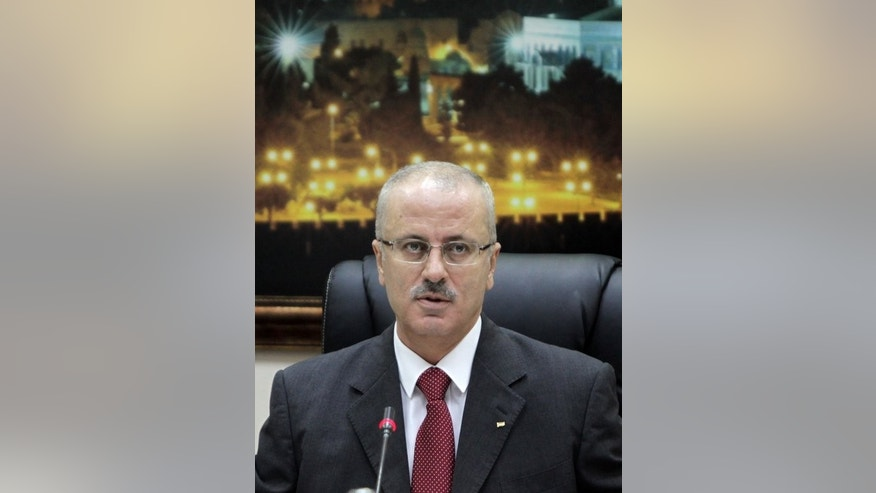 Palestinian Prime Minister Rami Hamdallah chairs a cabinet meeting in the West Bank town of Ramallah, on June 11, 2013. Palestinian president Mahmud Abbas has asked Hamdallah to stay on, tasking him on Tuesday with forming a new government.