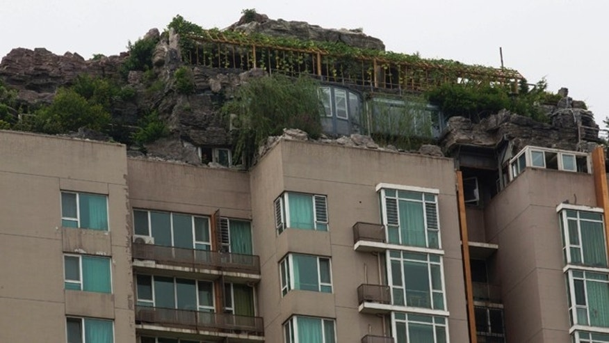 Aug. 13, 2013: A rooftop villa complete with rocks and flora built on top of a high rise residential building stands in Beijing, China. Beijing authorities are planning to demolish the bizarre rooftop villa embedded in rocks, trees and bushes that allegedly was built illegally atop a 26-story apartment block in the capital.