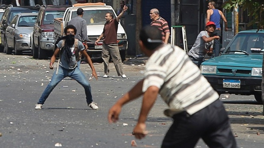 Aug. 13, 2013: A local resident, left, throws stones towards supporters of ousted President Mohammed Morsi during clashes in central Cairo. Clashes broke out in central Cairo on Tuesday when Morsi supporters came under attack as they marched to the Interior Ministry, a Reuters reporter said.