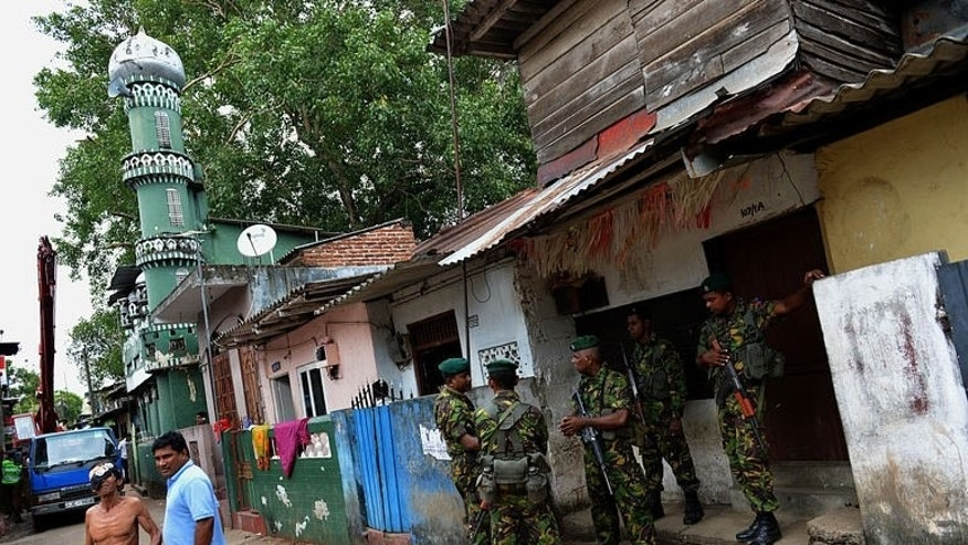 Sri Lankan paramilitary Special Task Force (STF) commandos stand guard outside the premises of a vandalized mosque in the capital Colombo on August 13, 2013. The European Union expressed concern on Tuesday at the state of political and religious freedom in Sri Lanka after a deadly army crackdown on a protest and the vandalising of a mosque.