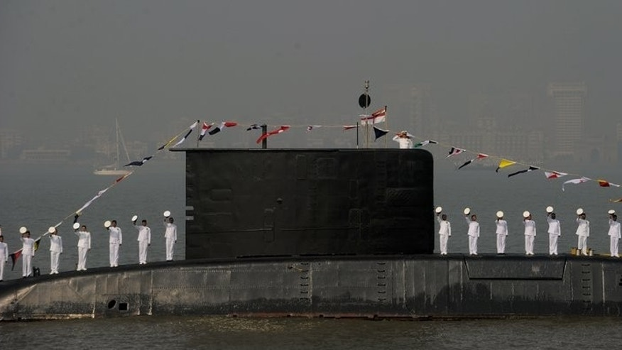 File photo shows Indian sailors standing on the deck of a submarine during a fleet review in Mumbai on December 20, 2011. A recently refurbished Indian submarine exploded early Wednesday in a dock in Mumbai, leaving rescuers scrambling to find 18 sailors who were on board.