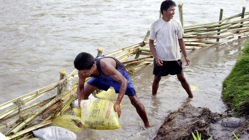 This file photo shows local residents attempting to divert flood waters away from paddy fields near Kathmandu, on June 10, 2003. According to the latest government figures, more than 100 people have been killed in floods and landslides triggered by rains during the monsoon in 2013, which runs from June to September.