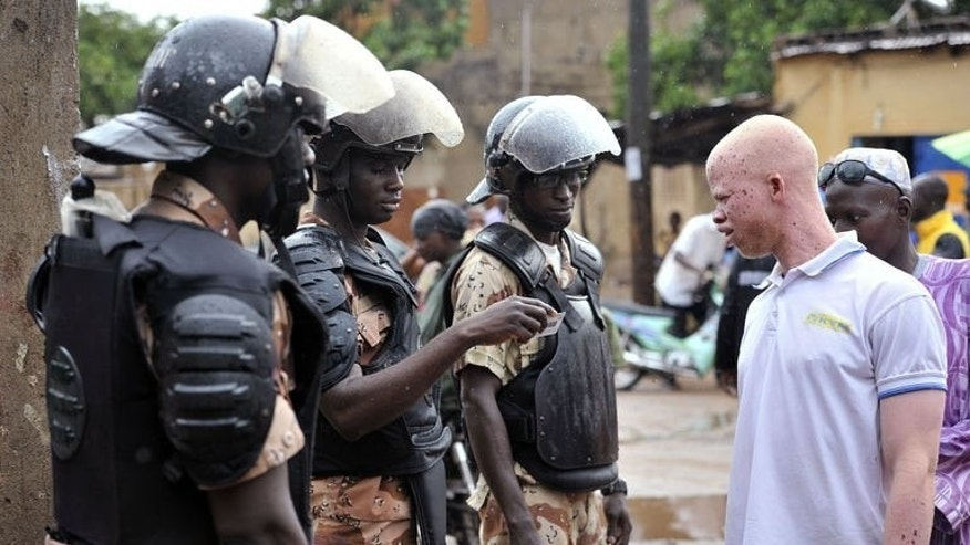 Police check ID's of people at a polling station during the presidential elections in Mali on August 11, 2013 in Bamako.