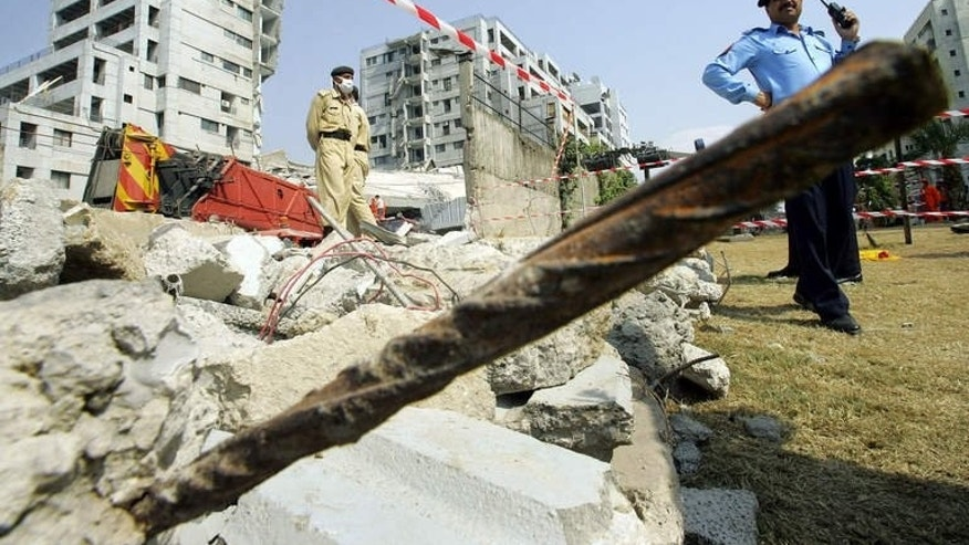 Pakistani police stand guard around the Margalla Towers while rescue workers continue to look for survivors after the building collpased after a powerful earthquake rattled Islamabad, on October 11 2005. A British architect of Pakistani origin -- who is wanted over the 2005 collapse of the Margalla Towers that killed 78 people -- has been arrested in Greece.