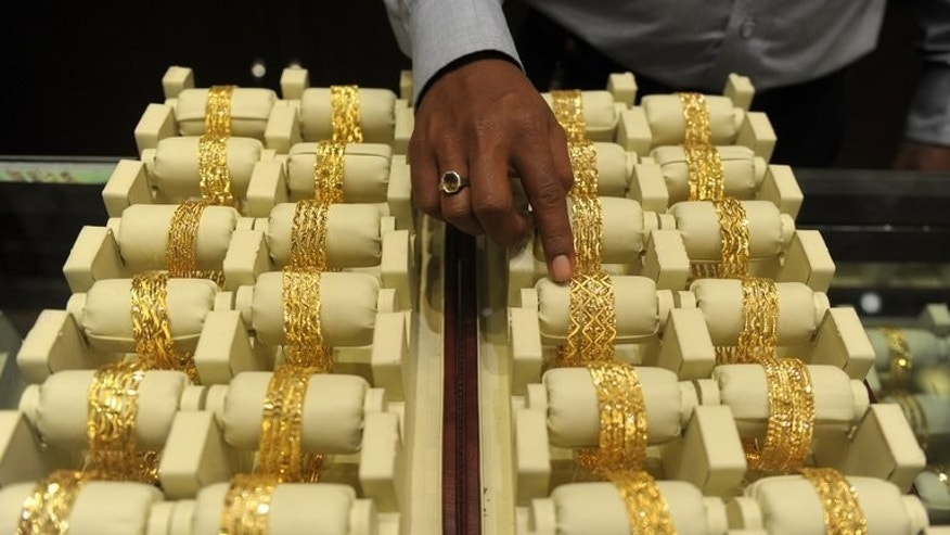 A sales assistant arranges gold bangles for display in a jewellery shop on the Hindu festival Akshaya Tritiya in Hyderabad, southern India on May 13, 2013. India, the world's biggest buyer of gold, raised duties Tuesday on bullion imports for the third time since January as it seeks to narrow the trade gap and defend the rupee.