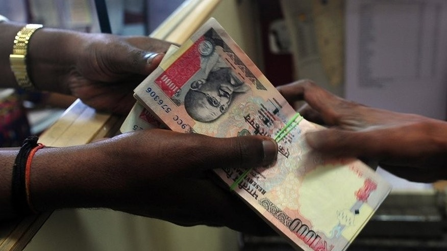 A customer receives a wad of Indian rupee notes from a foreign exchange dealer in Mumbai, on August 6, 2013. The rupee fell in early trade on Tuesday despite the government announcing new measures aimed at narrowing the current account deficit and aiding the ailing local currency.