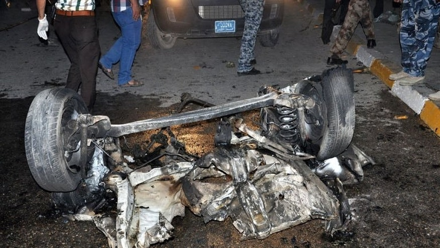 Iraqis inspect the remains of a vehicle at the scene of a car bomb explosion in Nasiriyah, on August 10, 2013. Attacks in Iraq have killed 13 people while militants bombed a major pipeline carrying oil to Turkey.