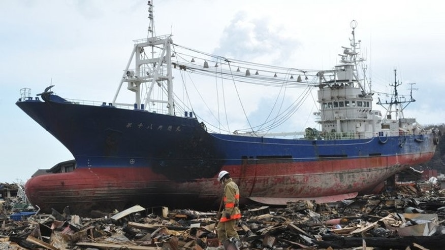 This file photo shows rescuers searching through debris in front of a large grounded ship, in Kesennuma, Miyagi prefecture, on March 17, 2011. The fishing boat that became one of the most poignant symbols of the tsunami disaster is to be scrapped, authorities announced on Tuesday.
