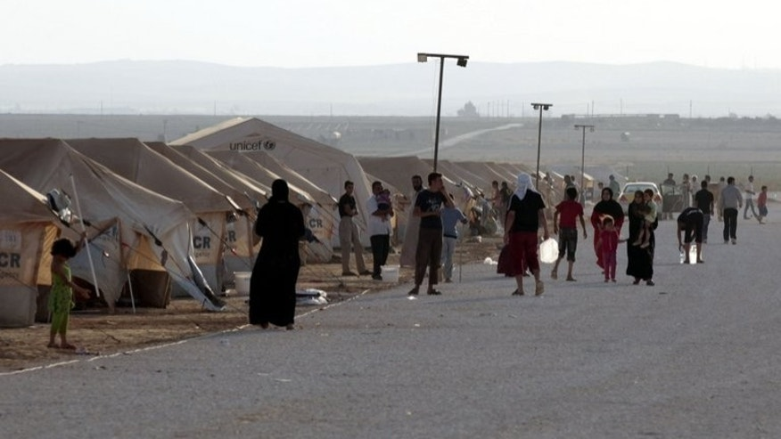 Syrian refugees gather at the Zaatari camp in Jordan, on July 31, 2012. Jordan has denied a UN report that organised crime networks operate in the country's Zaatari camp, which hosts 130,000 Syrian refugees.