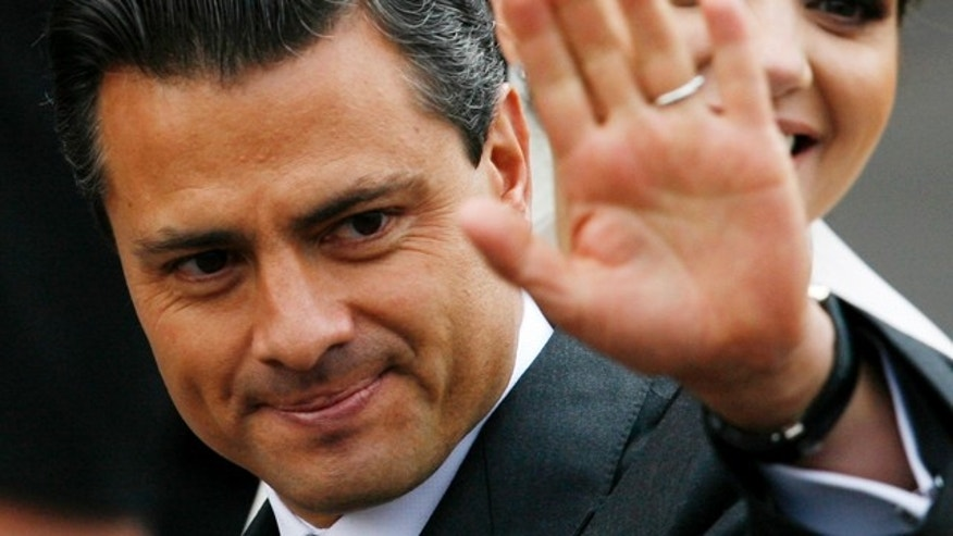 FILE - In this Nov. 27, 2010 file photo, Enrique Pena Nieto, governor of the state of Mexico, waves prior to his wedding with Mexican actress Angelica Rivera, behind, at the Metropolitan Cathedral in Toluca, Mexico. Pena Nieto, the former governor of Mexico State, told the Televisa network late Monday Sept. 19, 2011 that he plans to seek the nomination to run in the July 2012 presidential election for the Institutional Revolutionary Party, or PRI.  Pena Nieto, 45, is seen as the PRI's best chance to regain the presidency it held for more than 70 years before losing to Vicente Fox in 2000 and then Felipe Calderon in 2006, both of the rival National Action Party, or PAN.  (AP Photo/Marco Ugarte, File)
