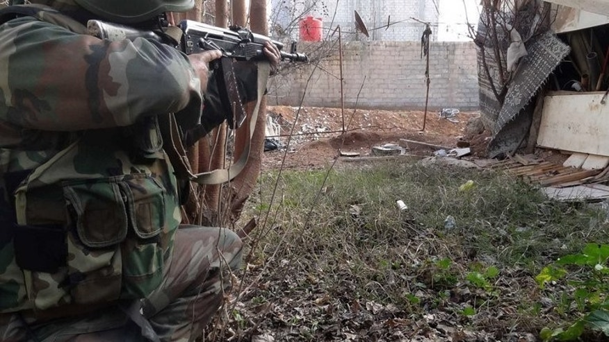 Syrian forces guard a position during fighting with rebels in Daraya, southwestern of Damascus, on January 22, 2013. A proposed international peace conference on Syria that aims to bring together President Bashar al-Assad's allies and the opposition will probably not happen until October at the very earliest, according to Russian Deputy Foreign Minister Gennady Gatilov.