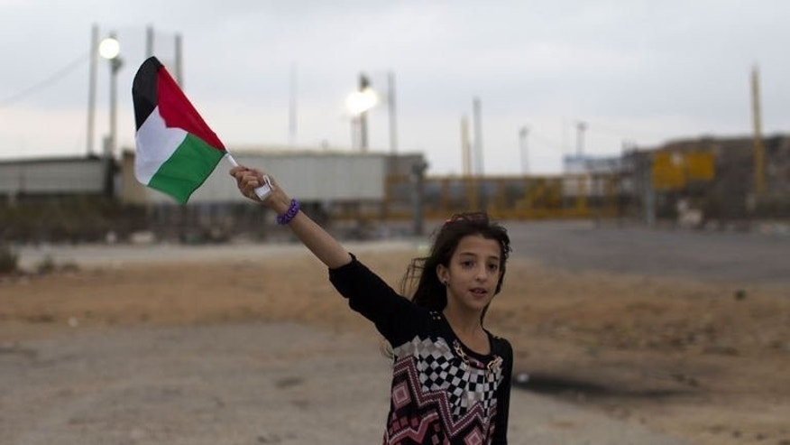 A Palestinian girl from the Israeli occupied West Bank waves the national flag close to the Israeli military prison of Ofer, in the village of Betunia, waiting for the release of Palestinian prisoners on August 13, 2013. An Israeli operation to free 26 Palestinian prisoners got under way late on Tuesday when two busloads of detainees left a jail near Tel Aviv.