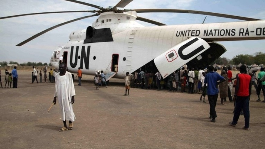 "People queue at the rear of a helicopter in Pibor in Sudan's Darfur. A helicopter and its crew contracted by peacekeepers in Sudan's Darfur have been ""detained"" be rebels in the troubled region for 10 days, the mission said."