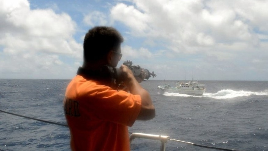 This video grab taken from a video released by the Philippines' National Bureau of Investigation (NBI) on August 13, 2013 allegedly shows Philippine coastguard personnel pointing a rifle at a Taiwanese fishing boat in disputed waters on May 9, 2013. A Taiwanese fishermen died in the incident and the NBI has recommended homicide charges be filed against eight Filipino coastguard personnel.