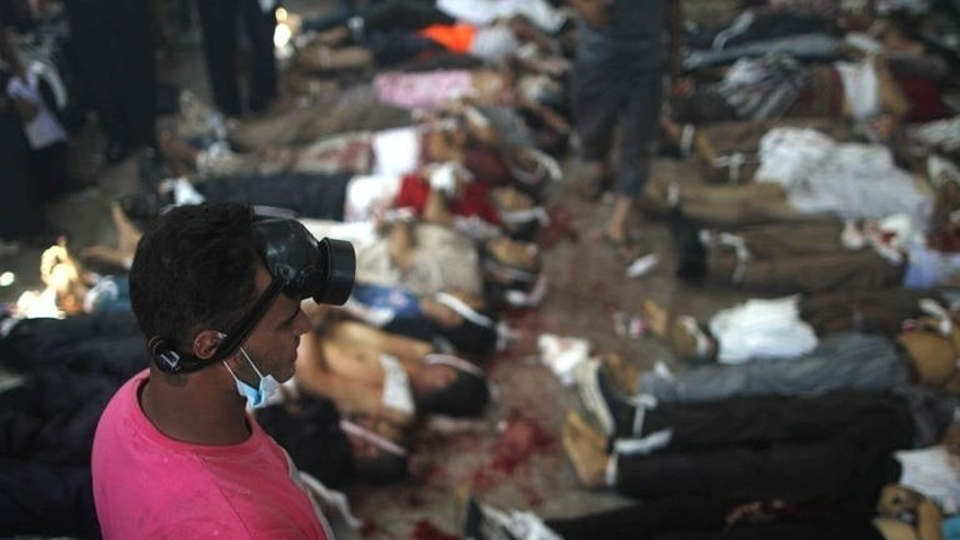 A man looks at bodies laid out in a make shift morgue after Egyptian security forces stormed two huge protest camps at the Rabaa al-Adawiya and Al-Nahda squares where supporters of ousted president Mohamed Morsi were camped, in Cairo, on August 14, 2013.