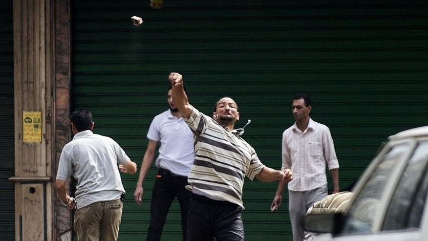 A supporter of ousted president Mohamed Morsi throws stones during clashes with residents and Egyptian riot police, in Cairo, on August 13, 2013. At least 17 people were killed on Wednesday as police moved in to disperse two huge protest camps in Cairo by supporters of Morsi.