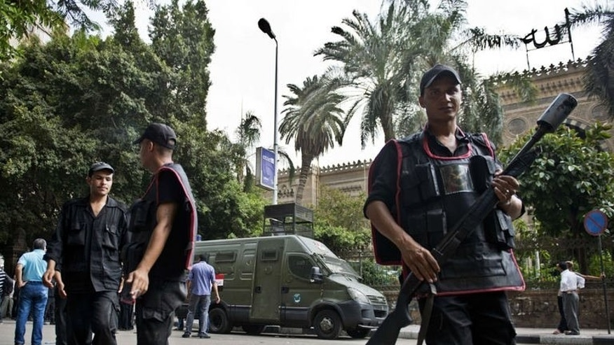 A riot policeman carries a tear gas grenade launcher as he walks in front of the ministry of religious endowments (Awqaf) in Cairo, on August 13, 2013, after clashes with members of the Muslim Brotherhood who were trying to attack the minister's office.