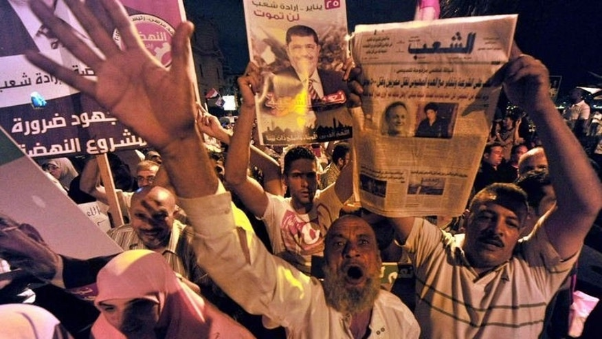 Muslim Brotherhood supporters shout slogans as they wave portraits of Egypt's ousted president Mohamed Morsi during a demonstration in the port city of Alexandria, on August 13, 2013, against the former leader's overthrow by the military.