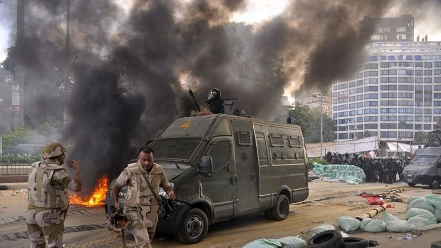 Egyptian riot police disperse a huge protest camp set up by supporters of ousted president Mohamed Morsi near Al-Nahda Square in Cairo, on August 14, 2013.