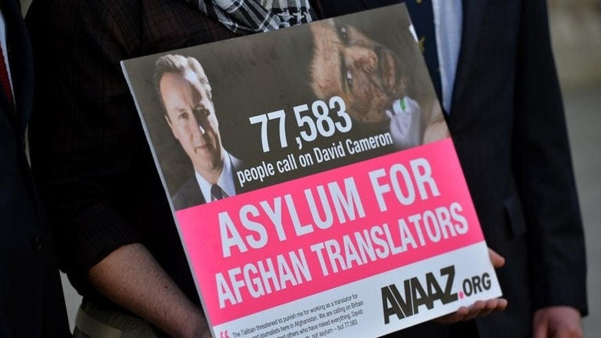 A man holds a petition in London calling for asylum for Aghan interpreters who served the British army on May 3, 2013. Winston Churchill's great-grandson delivered a petition with more than 70,000 signatures to Prime Minister David Cameron's office, demanding action to protect Afghan interpreters who have served with British troops.