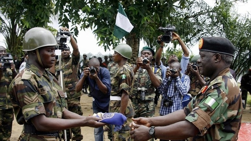 A soldier presents a Nigerian army flag to signify the country's withdrawal from the Bakassi Peninsula, August 14, 2006. Cameroon took full sovereignty over the disputed territory of Bakassi on Wednesday, state radio reported, five years after an agreement with Nigeria signalling the end of a bloody conflict over the land.