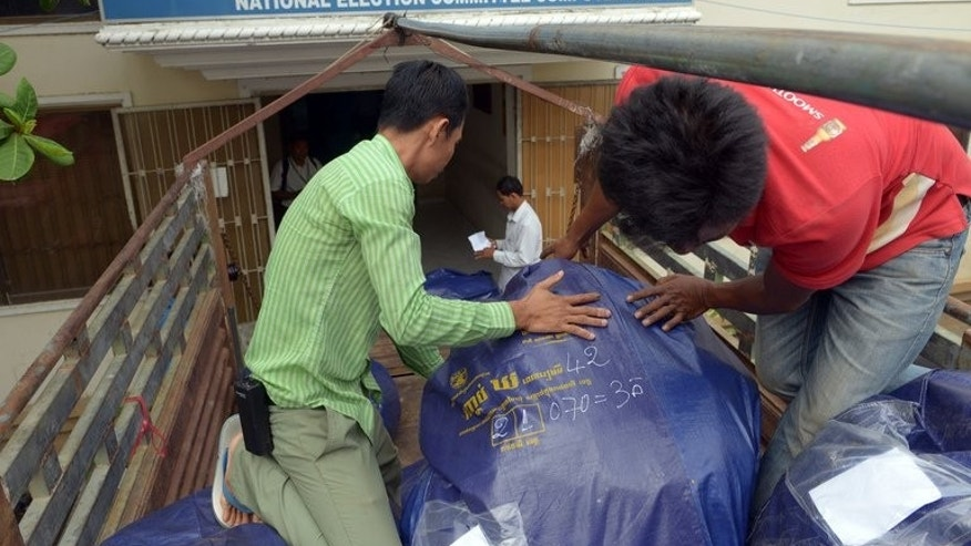 Cambodian National Election Committee officers pull a bag of used ballots from a truck at the NEC in Phnom Penh on August 3, 2013.
