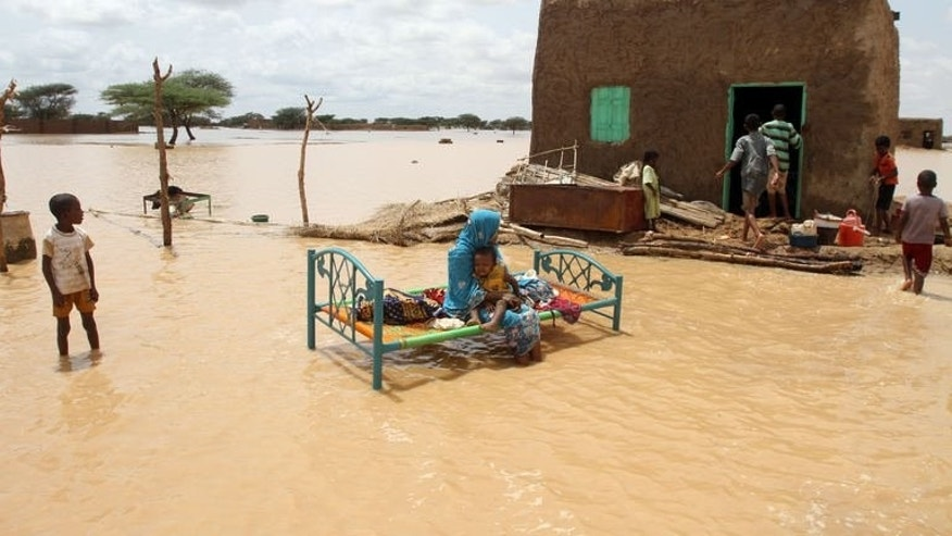 A Sudanese woman sits with her child next to her house in a flooded street on the outskirts of the capital Khartoum on August 10, 2013. Egyptian military planes landed in Khartoum on Wednesday as part of a regional aid effort for victims of flooding in Sudan this month that claimed dozens of lives.