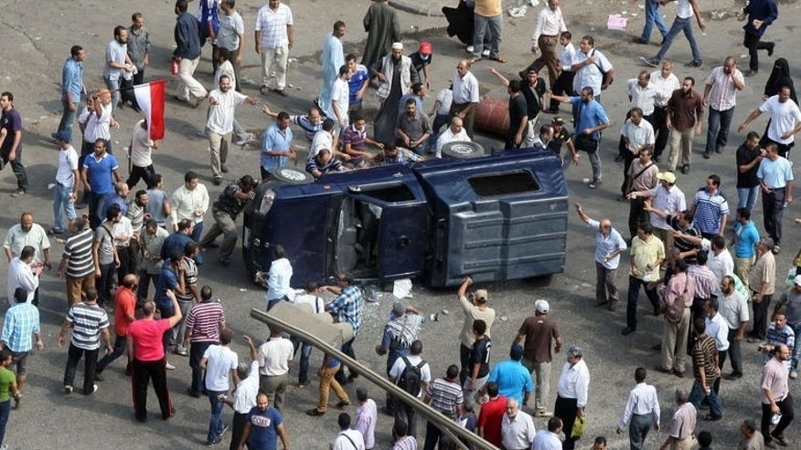 Muslim brotherhood supporters overturn a police vehicle in Cairo on August 14, 2013. European Union foreign affairs chief Catherine Ashton on Wednesday urged Egypt's rulers to end a month-long state of emergency imposed in the wake of a crackdown on supporters of ousted president Mohamed Morsi.
