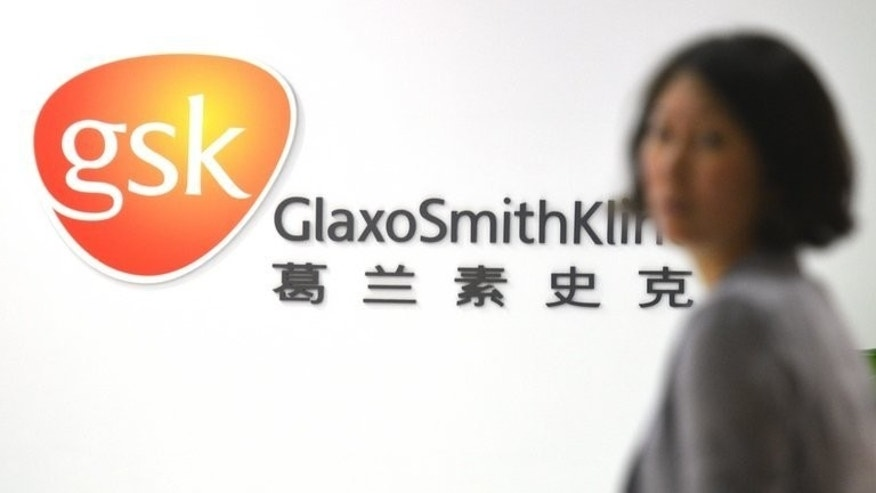 An employee of British drug firm GlaxoSmithKline enters their office headquarters in Shanghai on July 1, 2013. The most widely publicised inquiry by Chinese regulators is a bribery probe into GSK.