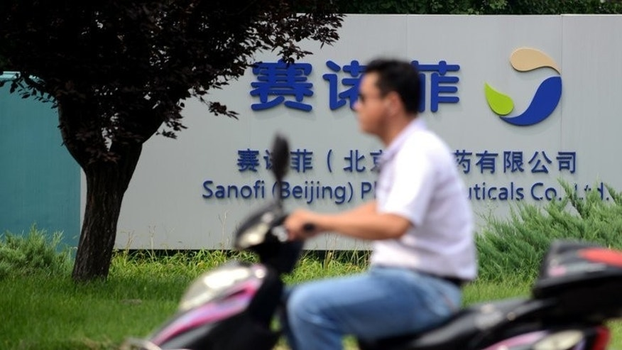 A man rides past the Sanofi offices in Beijing on August 13, 2013. France's Sanofi is being investigated over reports it bribed more than 500 doctors, according to state media.