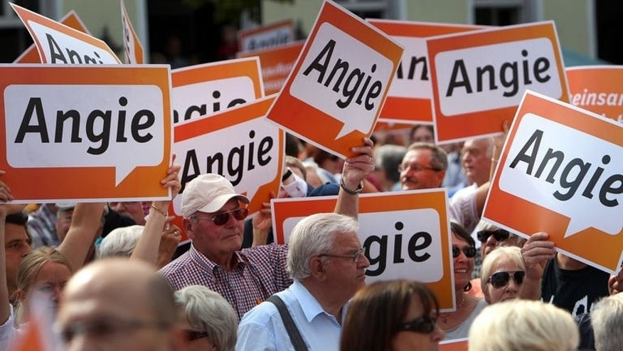 Supporters of German Chancellor Angela Merkel attend a CDU party rally in Seligenstadt, central Germany, on August 14, 2013. Merkel chose a picturesque small town to launch into full campaign mode for an election in which she is seen likely to stay at the helm of Europe's biggest economy.